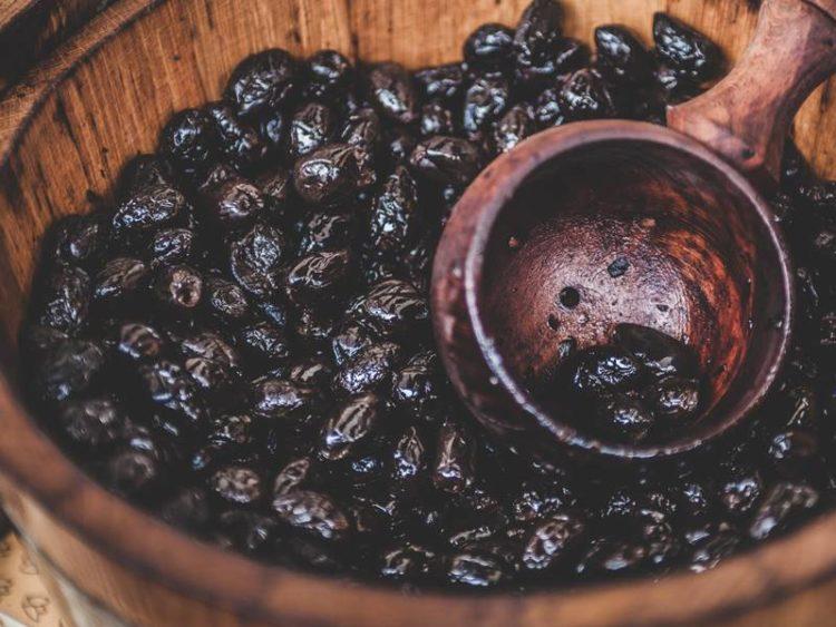houten bak met houten lepel met zwarte olijven