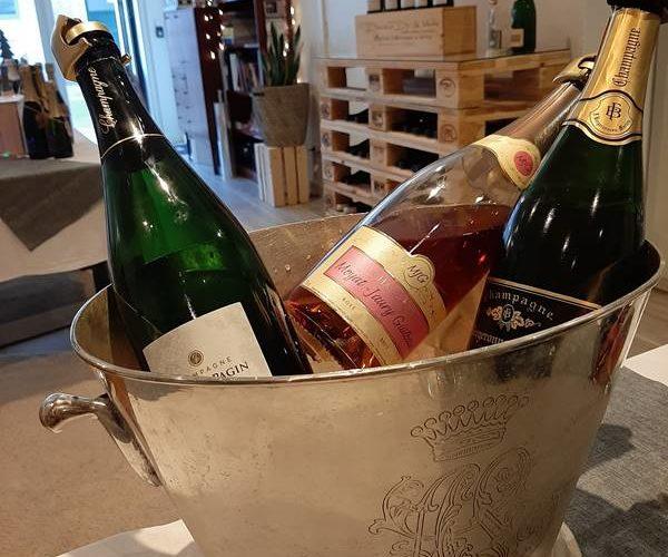 drie flessen champagne in een zilveren wijnkoeler