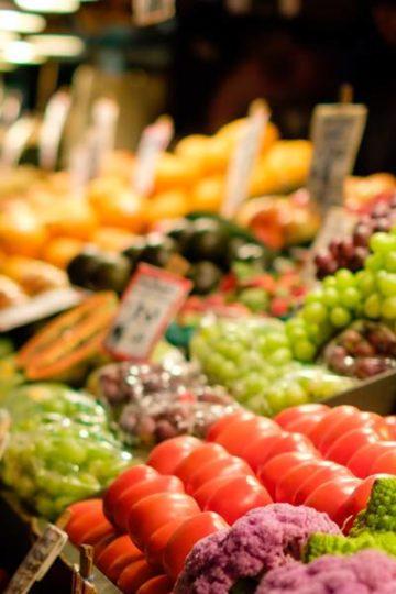 groente stal met druiven tomaten, paarse bloemkool met wazige achtergrond