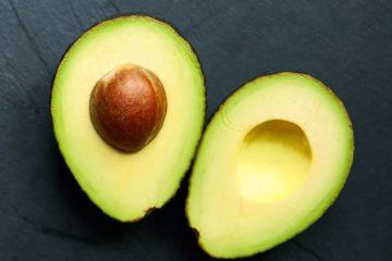 2 halve avocado's op zwarte leisteen achtergrond