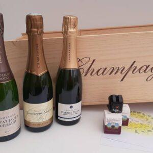 drie halve flessen met 3 bubbelsstoppen voor een grote houten kist met opdruk champagne